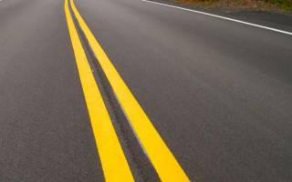 Желтая разметка на дороге вдоль бордюра